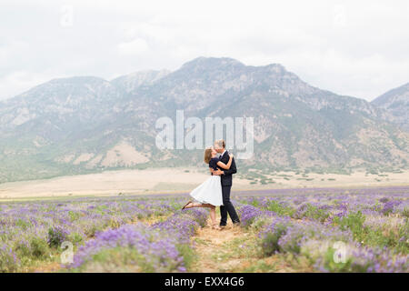 Newlywed couple kissing in lavender field with mountains on background - Stock Photo