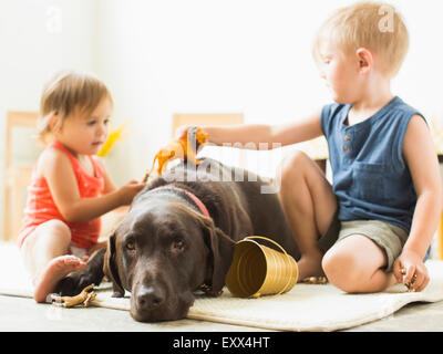 Children (2-3) playing with dog - Stock Photo
