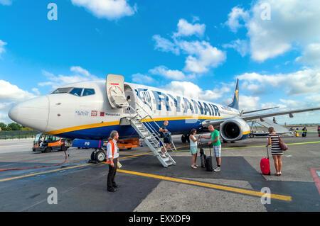 PISA, ITALY - AUGUST 21, 2014: passengers deplane Ryanair Jet airplane after landing in Pisa airport, Italy. - Stock Photo