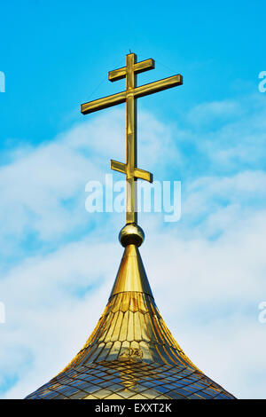 Cross on the dome of the Orthodox Church against the blue sky - Stock Photo