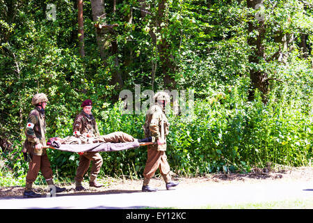 Wounded soldier carried on stretcher hurt injured shot hit lifeless incapacitated carrying British army re-enactment - Stock Photo