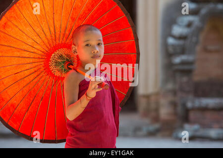 Buddhist novice monk holding umbrella at entrance to Sulamani Temple, Myanmar - Stock Photo