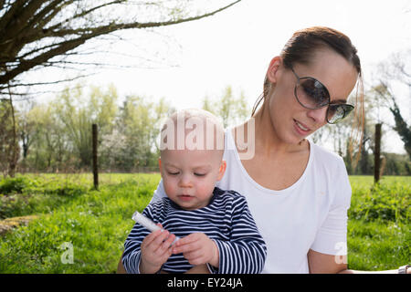 Baby boy sitting on mothers lap in field - Stock Photo