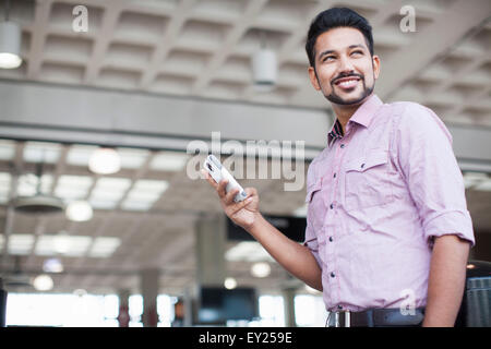 Low angle view of young man using smartphone in train station - Stock Photo