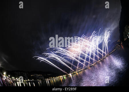 Fireworks on the Lugano Lake in a summer evening seen from lakefornt of Lavena-Ponte Tresa, Lombardy - Italy - Stock Photo