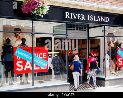 Two younger women enter the River Island shop in the High Street, Winchester, Hampshire possibly attracted by the - Stock Photo