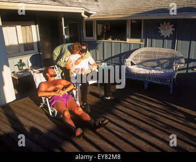 Coastal homes and sun bathers at Woods Cove in Laguna Beach on a warm winter day in  Southern California sunbathing - Stock Photo