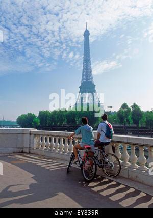 Couple sitting on bikes looking toward Eiffel Tower in Paris - Stock Photo