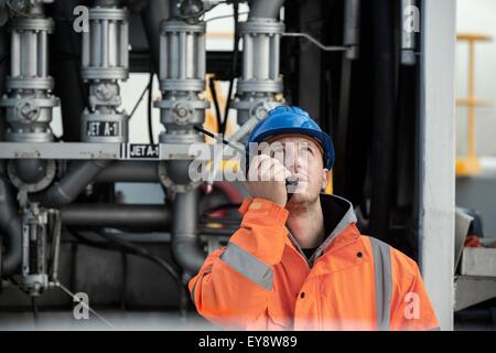 Male worker speaking on two way radio at fuel depot - Stock Photo
