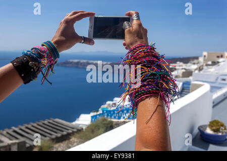 A large number of knitted woman bracelets on the girl's hands, A woman takes pictures on her phone Santorini landscape - Stock Photo