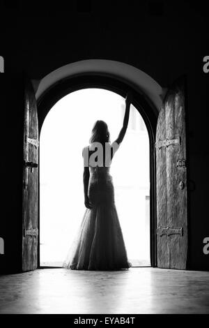 Beautiful bride standing in the middle of a wooden wide open door, with right hand high. Black and white image with - Stock Photo