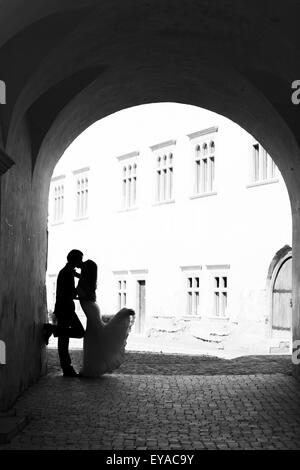 Newlywed couple kissing in a gangway. Black and white image with grain added as effect. - Stock Photo