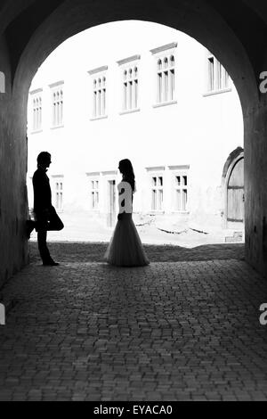 Newlywed couple staring one another in a gangway. Black and white image with grain added as effect. - Stock Photo
