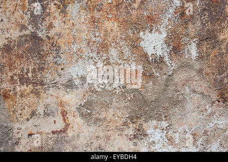 Abstract background of old painted plastered wall with peeling paint texture in brown, grey, and orange colors - Stock Photo