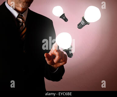 Business man pointing on a light bulb, new idea concept - Stock Photo