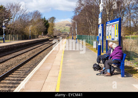 People waiting for a train on the platform at Hope Railway Station in the countryside. Derbyshire, Peak District - Stock Photo