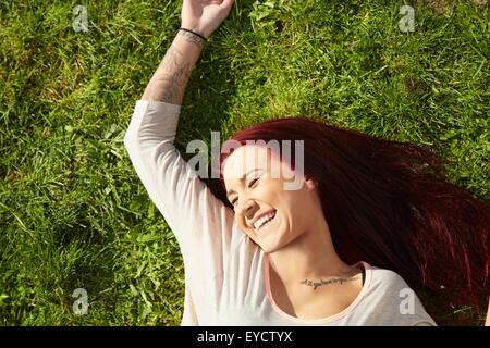 Overhead view of young woman lying on grass laughing - Stock Photo