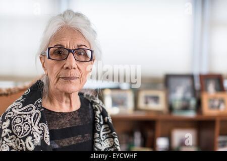 Portrait of senior woman wearing eyeglasses at home - Stock Photo