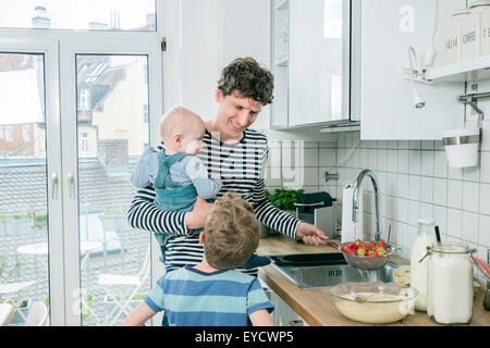 Father prepares food while holding baby in kitchen - Stock Photo