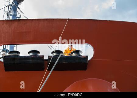 Worker fastening ropes to mooring posts on oil tanker deck - Stock Photo