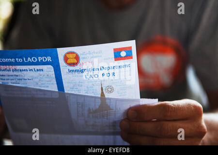 Filling out the various Visa paperwork to exit Thailand and enter Laos; Chiang Mai, Thailand - Stock Photo
