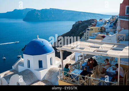 View of the Aegean sea and buildings on the hillside above; Oia, Santorini, Greece - Stock Photo