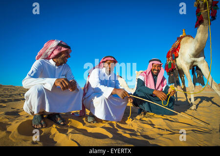 Relaxing with camels; Madain Saleh, Saudi Arabia - Stock Photo