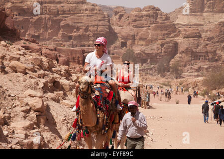 Tourists on camels riding along the colonnaded street; Petra, Jordan - Stock Photo