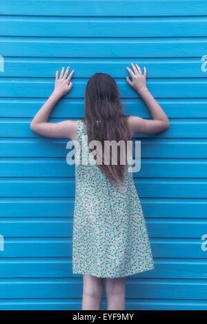 a girl with a floral dress is leaning against a wooden wall - Stock Photo