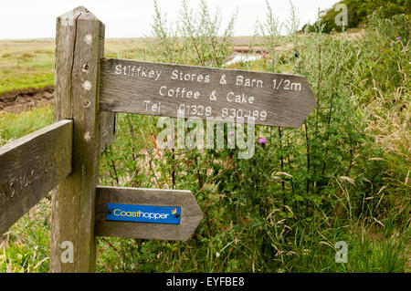 A signpost on the Norfolk Coast Path points to the Stiffkey Stores & Barn and a stop for the Coasthopper bus. - Stock Photo