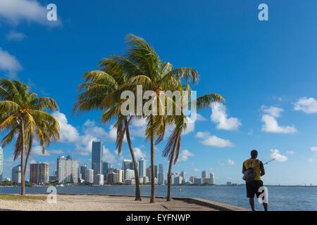 MAN ALONE FISHING BRICKELL AVENUE SKYLINE FROM RICKENBACKER CAUSEWAY DOWNTOWN MIAMI FLORIDA USA - Stock Photo
