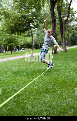 Almaty, Kazakhstan - 04,07,2013: slacklining in the park in the evening - Stock Photo
