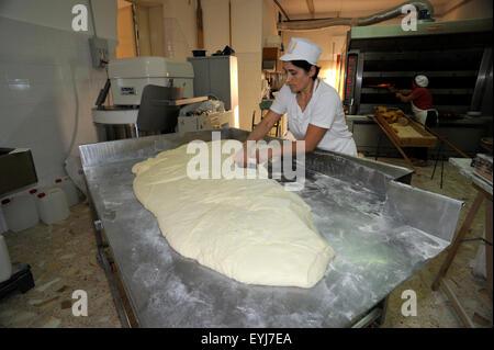 italy, basilicata, bakery, baker kneading bread - Stock Photo