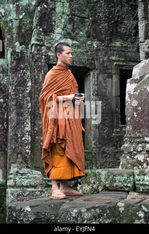 SIEM REAP, CAMBODIA - OCTOBER 30, 2014: Buddhist monk stands among the weathered temple architecture at Bayon in - Stock Photo