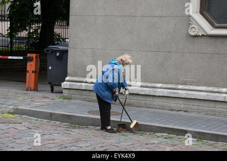 A woman sweeping the street early one morning in Tallinn, Estonia's old town. - Stock Photo