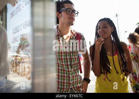 Young couple reading food stall menu, Copacabana, Rio De Janeiro, Brazil - Stock Photo