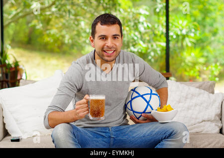 Hispanic man wearing denim jeans with grey sweater sitting in sofa enthusiastically watching tv holding beer and - Stock Photo