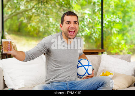 Hispanic man wearing denim jeans with grey sweater sitting in sofa enthusiastically cheerful facial expression watching - Stock Photo