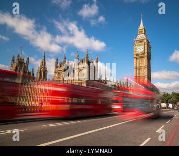 Big Ben in Westminster with red London Buses going past during the day. There is space for text in the image - Stock Photo