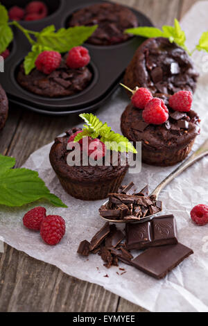 Chocolate raspberry yogurt muffins with pieces of chocolate and muffin tin - Stock Photo