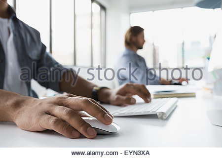 Businessmen working at computers in office - Stock Photo