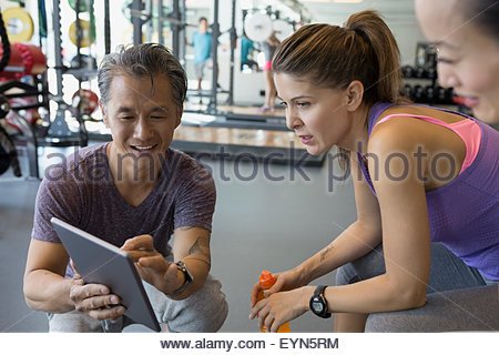 Personal trainer digital tablet talking to women gym - Stock Photo