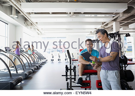 Personal trainer digital tablet talking to man gym - Stock Photo