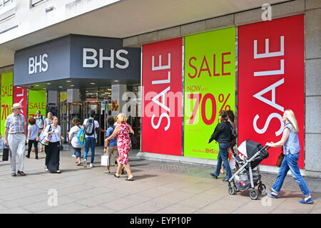 Oxford Street Shoppers and BHS store windows covered in summer sale discount posters - Stock Photo