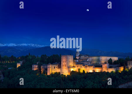 Moonrise over lit hilltop Alhambra Palace fortress complex at twilight Granada with snow capped Sierra Nevada Mountains - Stock Photo