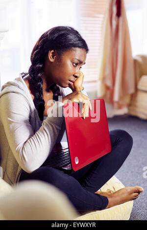 Frustrated ethnic girl sat indoors - Stock Photo