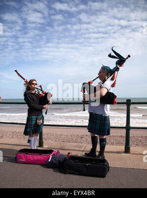 Sidmouth, Devon, UK. 4th Aug, 2015. A busking couple play traditional Scottish music on bagpipes along the Esplanade - Stock Photo
