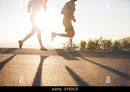 Low angle view of two people running on country road at sunrise. Cropped shot of young man and woman jogging in - Stock Photo