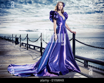Young woman wearing a beautiful long blue evening gown standing at waterfront, artistic fashion portrait - Stock Photo