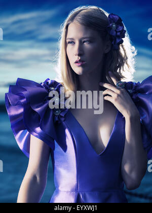 Beauty portrait of a young beautiful blond woman wearing a blue evening dress outdoors - Stock Photo